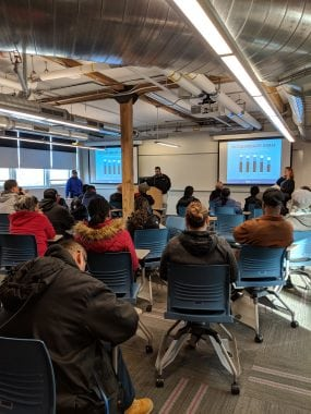 image of custodian sustainability training, a room full of people looking at a powerpoint presentation with a graph showing campus sustainability goals